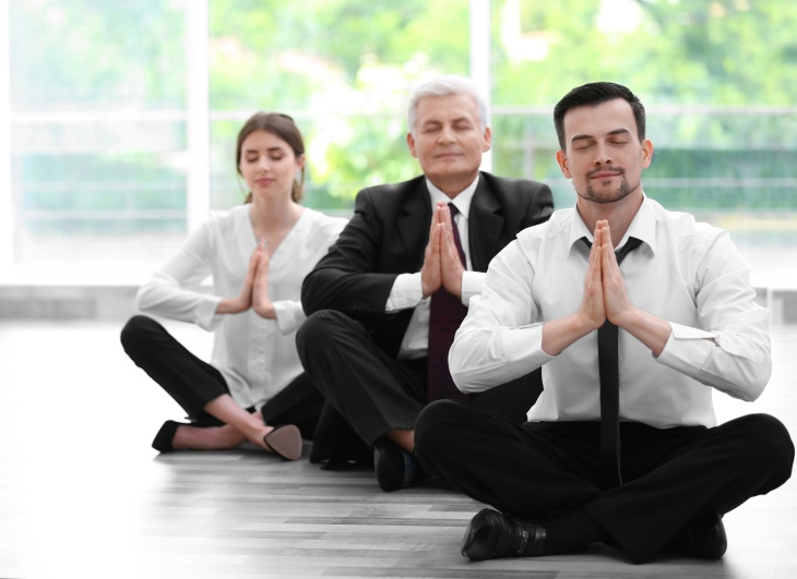 Business people relaxing in meditation pose in office