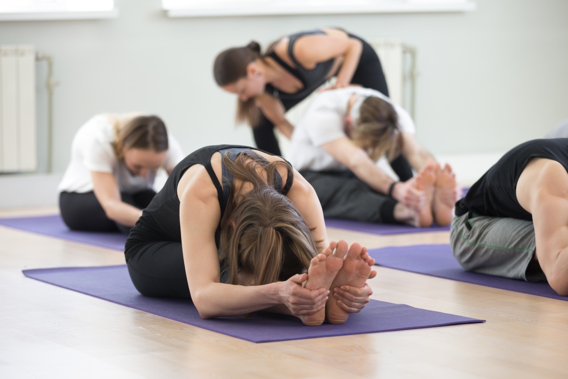 Young female yoga instructor teaching paschimottanasana