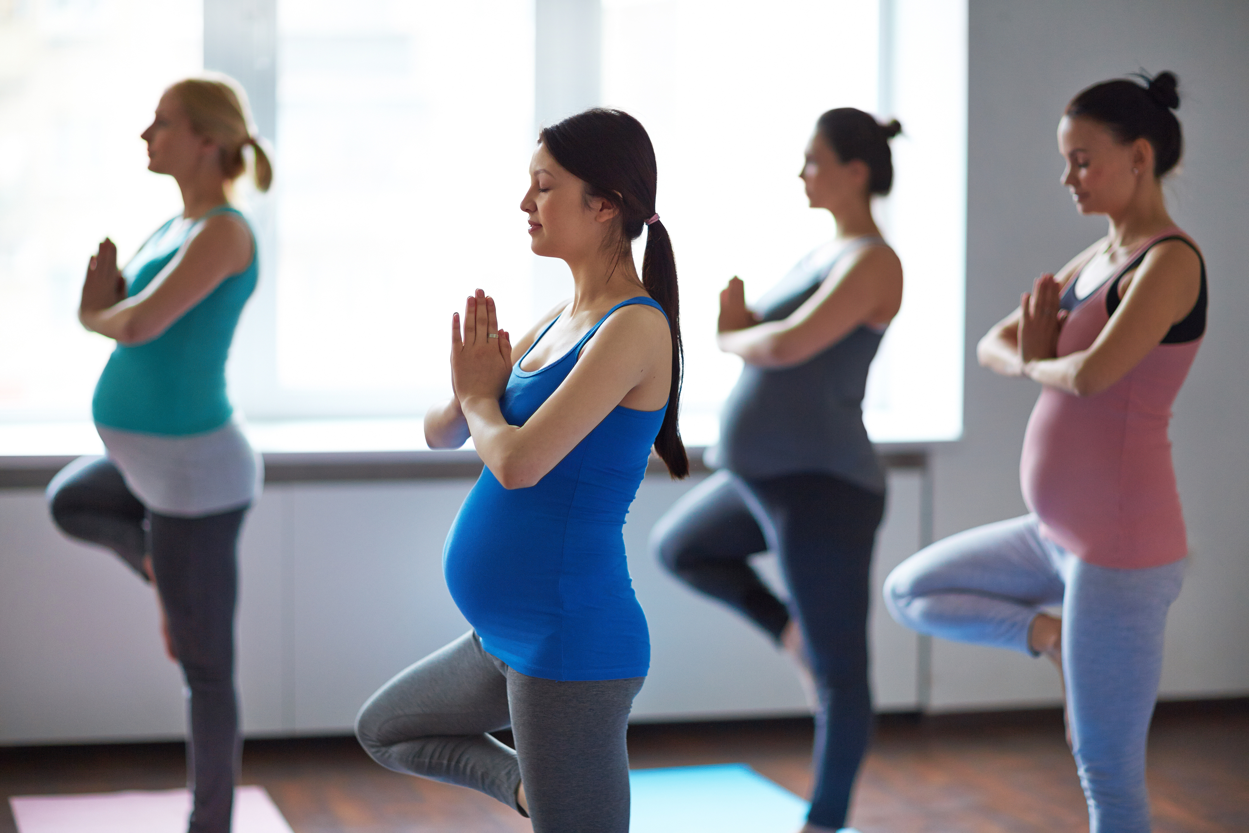 Pregnant women practicing yoga tree pose