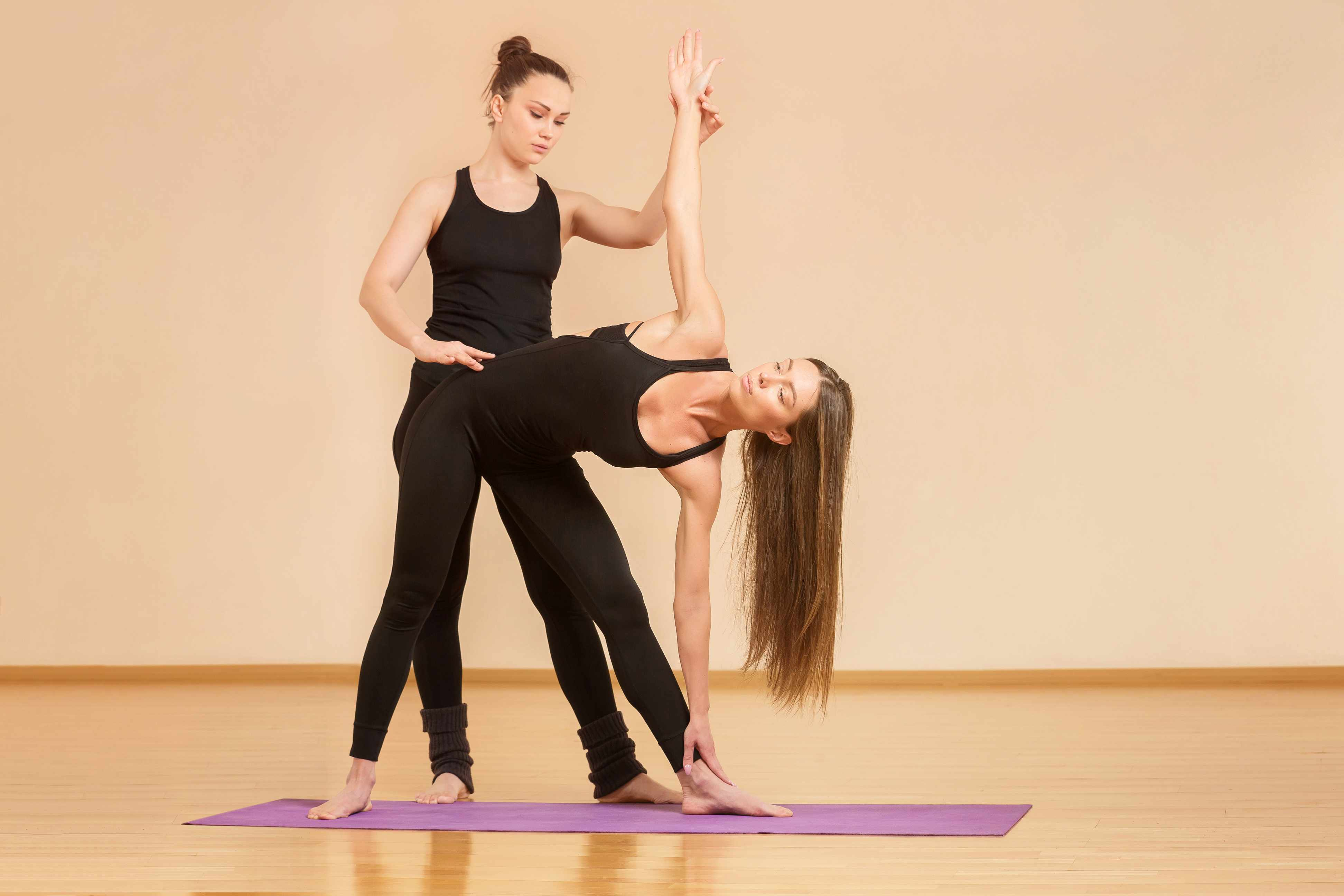 Teacher assisting student in a yoga pose